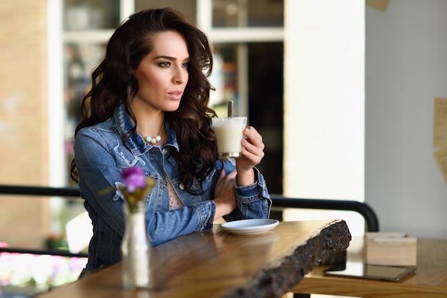 창문을 통해 보이는 도시 카페에서 실내에 앉아있는 여자