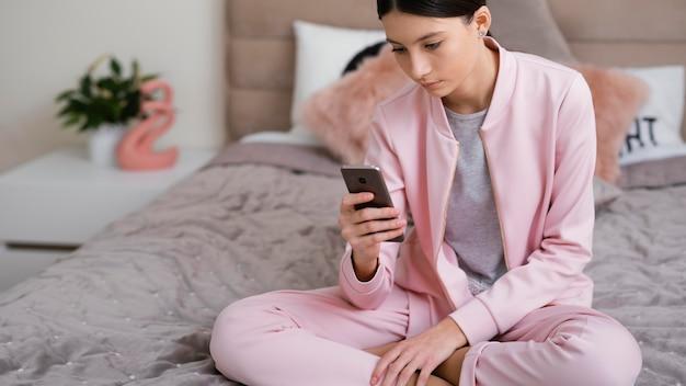 屋内に座って携帯電話を使用している女性