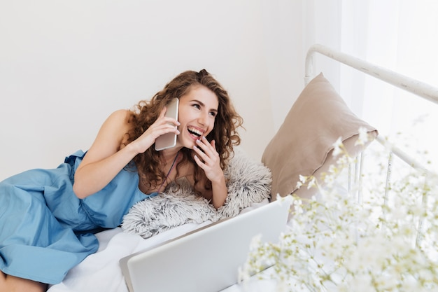 Woman sitting indoors on bed talking by phone. looking aside.