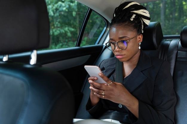 Женщина сидит в своей машине и смотрит на смартфон