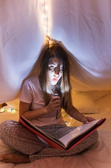 Woman sitting inside the bed under curtain reading magazine holding torch light over her face