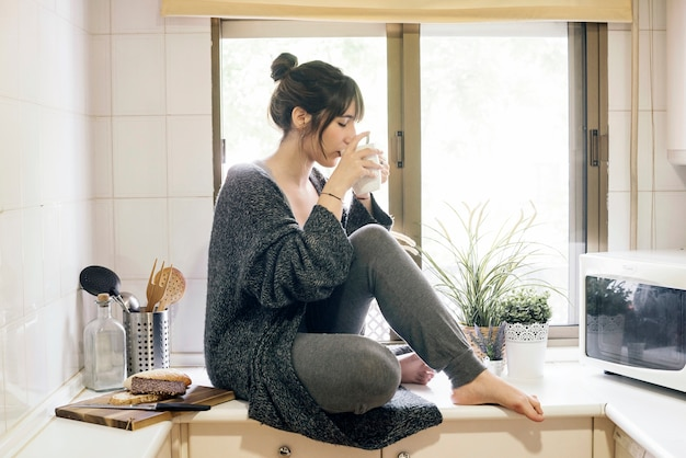 Woman sitting on kitchen countertop drinking coffee