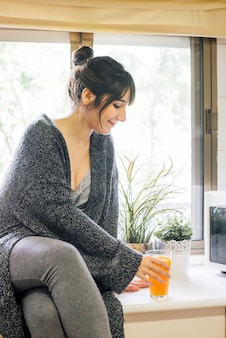 Woman sitting on kitchen countertop with glass of juice