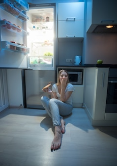 Woman sitting on kitchen floor next to open refrigerator and eating pizza