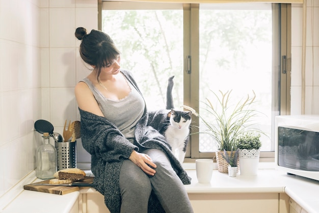 Woman sitting in kitchen with her cat
