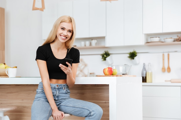 Woman sitting in kitchen with phone