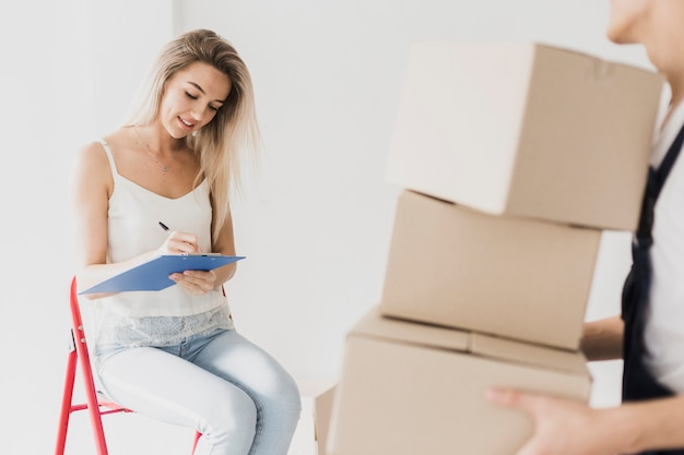 Woman sitting on ladder planning relocation
