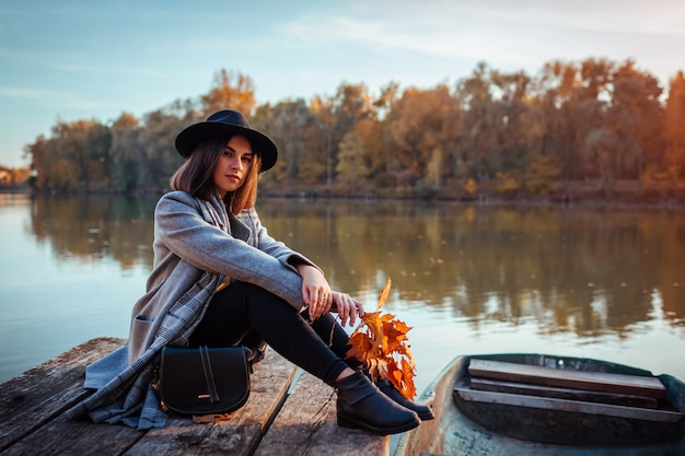 Woman sitting on lake pier by boat admiring autumn landscape. fall season activities