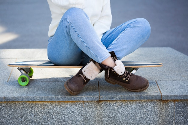 Woman sitting on longboard with legs crossed