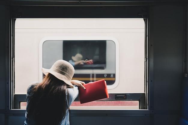 여자가 앉아 빨간 책을 읽고 여행을 즐기는 창 밖을 봐. 기차 여행