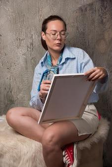 Donna seduta che guarda su tela con pennello su marmo