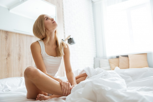 Woman sitting and looking up on bed in bedroom