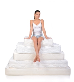 Woman sitting on a lot of mattresses.