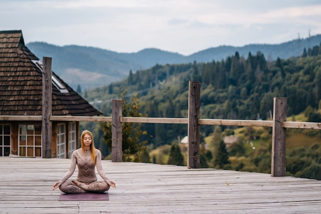 A woman sitting in lotus position at the morning on a fresh air.