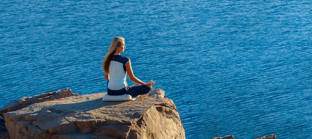Woman sitting in lotus position on rock above the sea and meditating. yoga outdoor. copyspase