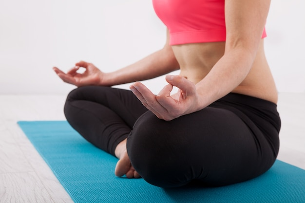 Woman sitting in lotus position, yoga indoors.