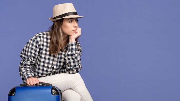 Woman sitting on luggage with copy-space