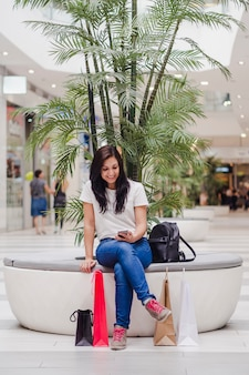 Woman sitting in the mall looking at her mobile phone and smiling, with some shopping bags on the floor.