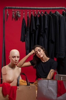 Woman sitting next to mannequin