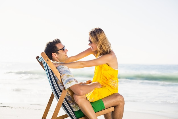 Woman sitting on mans lap at beach