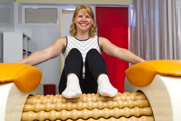 Woman sitting on the massage tool for the legs with a big joy on her face
