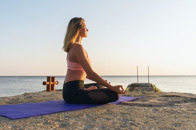 Woman sitting on a mat in a lotus position in the evening on the seashore is engaged in meditation