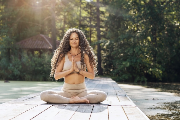 A woman sitting on a mat in a lotus position meditates on a wooden bridge near a pond