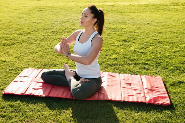 Woman sitting and meditating in lotus pose outdoors