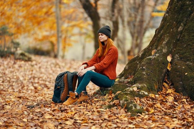 여자가 숲에서 나무 근처에 앉아 떨어지는 나뭇잎 풍경 공원