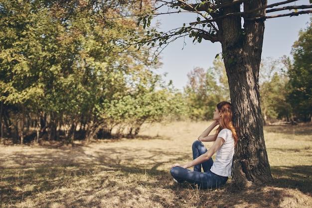木の太陽の自由の旅の近くに座っている女性