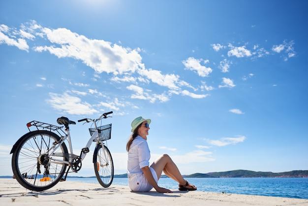 Женщина сидит возле велосипеда на каменистом тротуаре под голубым небом