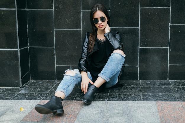 Женщина, сидящая возле черной стены