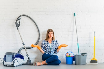 Woman sitting near cleaning equipments in front of brick wall