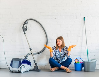 Woman sitting near cleaning equipments shrugging