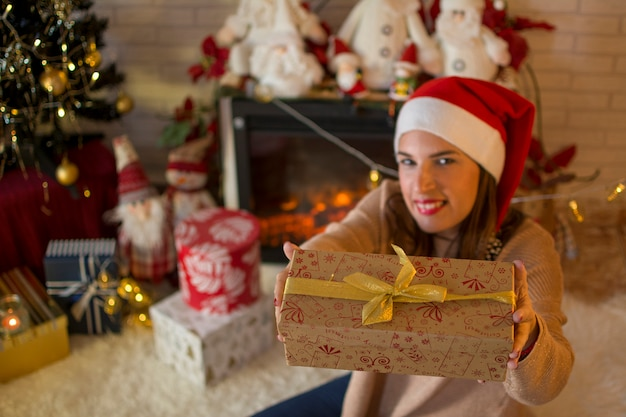 Woman sitting near the fireplace, happily offering a christmas gift box