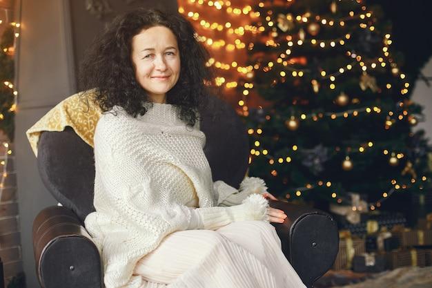 Женщина, сидящая у камина. дама в белом свитере. брюнетка в рождественской концепции.