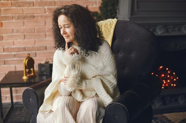 Donna seduta vicino al camino. signora in un maglione bianco. bruna in un concetto di natale.
