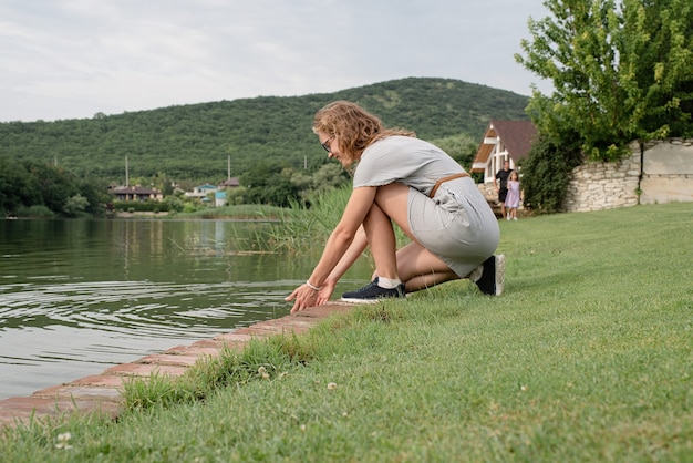 Woman sitting near the lake, looking away