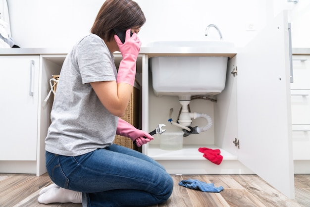 Woman sitting near leaking sink in laundry room calling for help