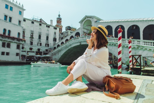 Woman sitting near rialto bridge in venice italy looking at grand canal with gondolas summer time copy space