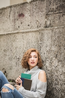 Woman sitting near stone wall and holding notebooks