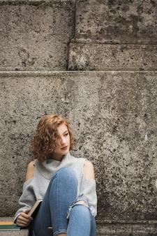 Woman sitting near stone wall