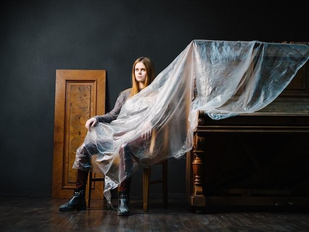 Женщина, сидящая возле пианино на стуле интерьерный романтический музыкальный инструмент