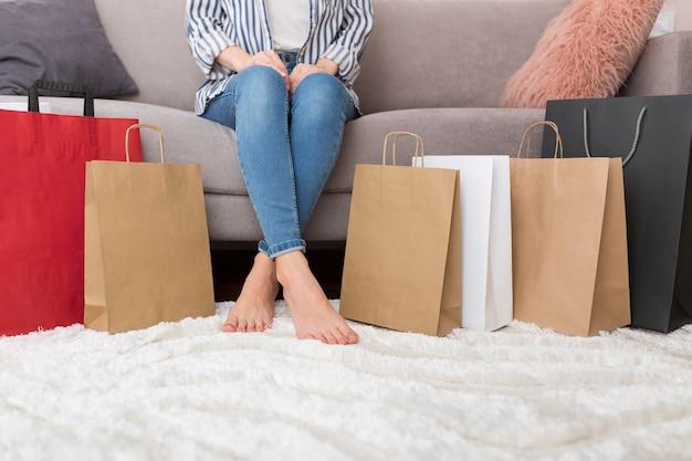 Женщина, сидящая рядом с хозяйственными сумками