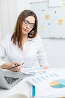 A woman sitting in an office works with financial reports and charts.
