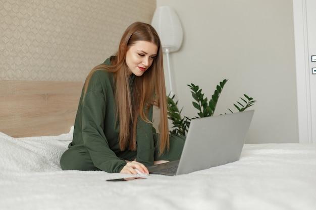 Женщина сидит на кровати и использует ноутбук