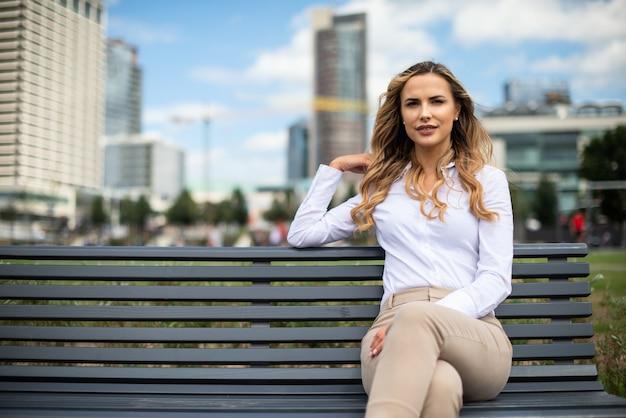 屋外のベンチに座っている女性