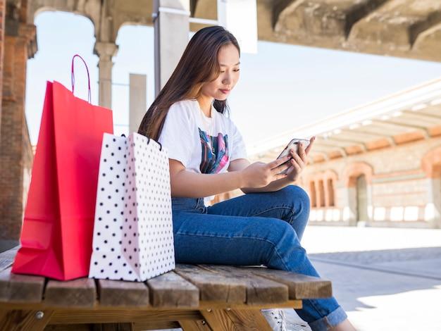 여자가 그녀의 쇼핑백과 함께 앉아 벤치에 앉아