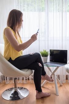 窓の近くのテーブルにラップトップで彼女の携帯電話を保持している椅子に座っている女性
