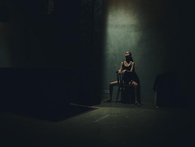 屋内の孤独うつ病の対立の壁にもたれて椅子に座っている女性